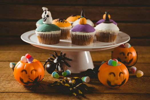 Cup cakes with decorations on wooden table during Halloween