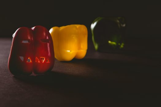Colorful carved bell peppers on table