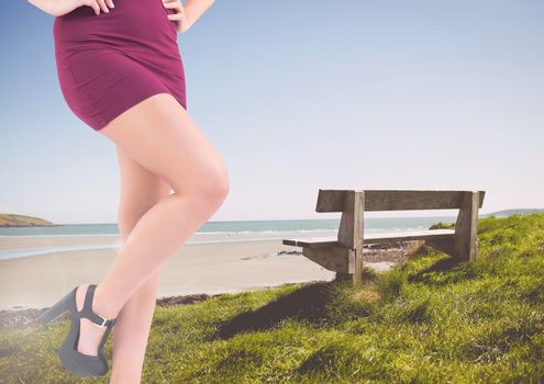 Sexy woman's legs by a bench at the sea