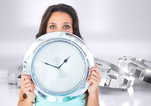 Woman holding chrome clock in front of chrome silver cog wheels