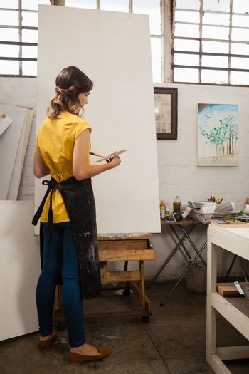 Woman painting on canvas