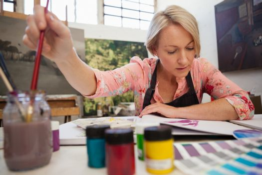 Woman selecting a paintbrush