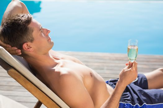 Young man holding champagne flute by the swimming pool