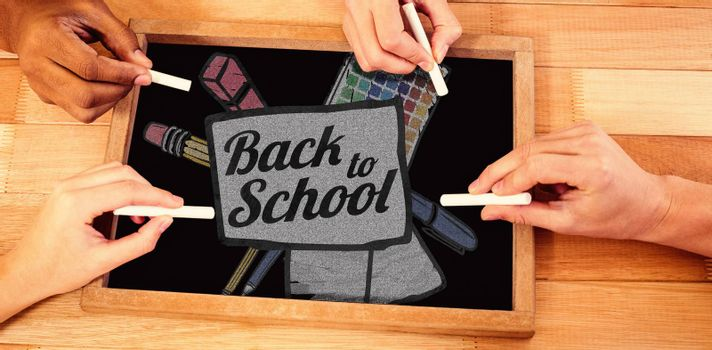 Back to school text on paper with pen against hands writing on chalkboard