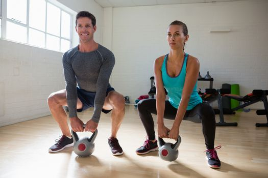 Athletes lifting kettlebells in health club
