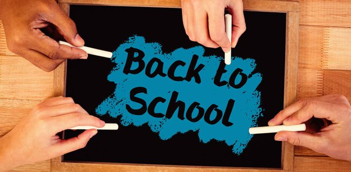 Back to school text on pink splash against hands writing on chalkboard