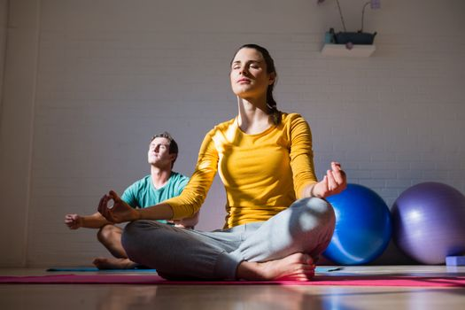 People meditating in health club