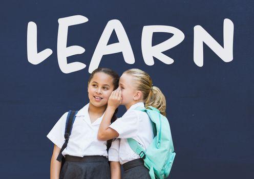 Learn text on blackboard with schoolgirls whispering