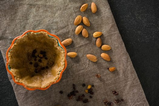 Raisin being stuffed in tart with almond on wax paper