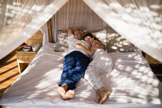 Couple relaxing in canopy bed