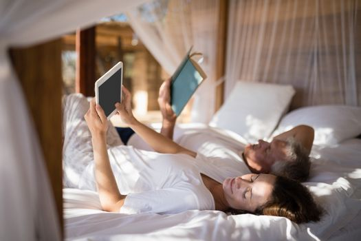 Couple relaxing on canopy bed