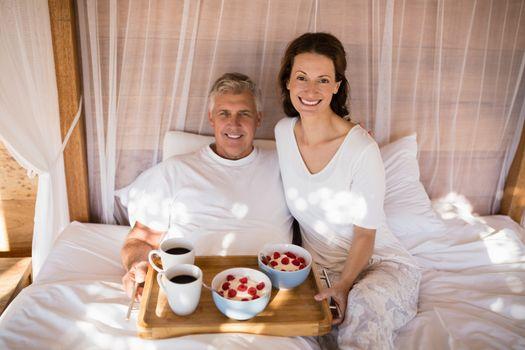 Happy couple having breakfast in canopy bed