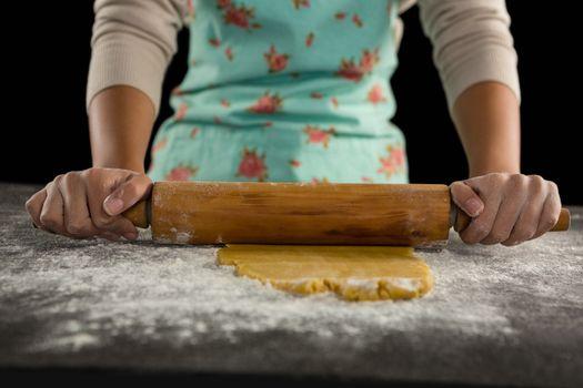 Woman baking dough with rolling pin
