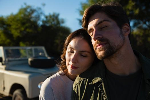 Couple with eyes closed by vehicle