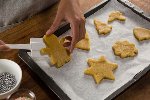 Man placing gingerbread cookies in baking tray