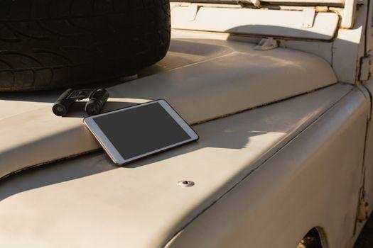 Tablet and binocular on vehicle hood