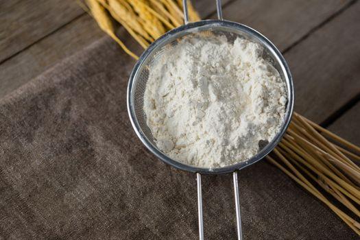 Flour inside sieve placed over wheat stem