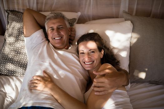 Happy couple relaxing in canopy bed