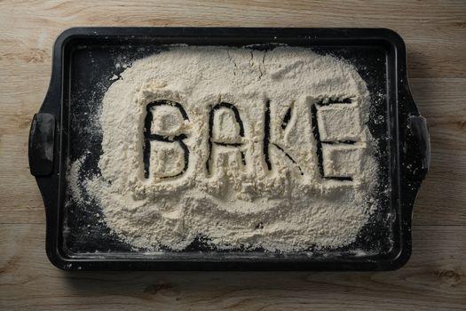 The word bake written on flour on a baking tray