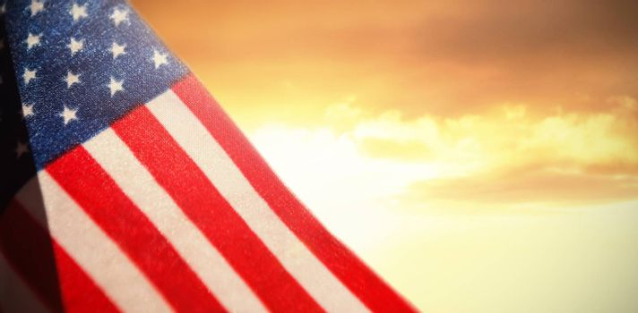 Close-up of American flag against scenic view of sea against sky during sunset