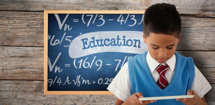 Schoolboy using digital tablet against education against blue chalkboard