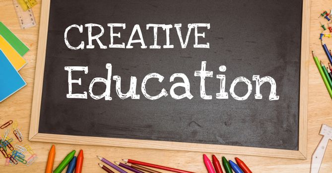 Digital composite of Creative education text on blackboard