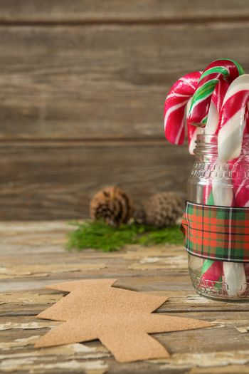 Pine cones and candy cane in jar against wooden plank