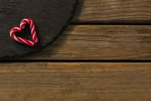 View of candy cane arranged in heart shape on wood