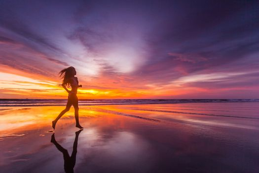 Picture of sexy female running on the beach, in a stylish bikini enjoying summer vacation at sunset copy space background
