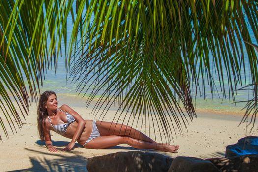 Woman in bikini laying on tropical beach under palm trees