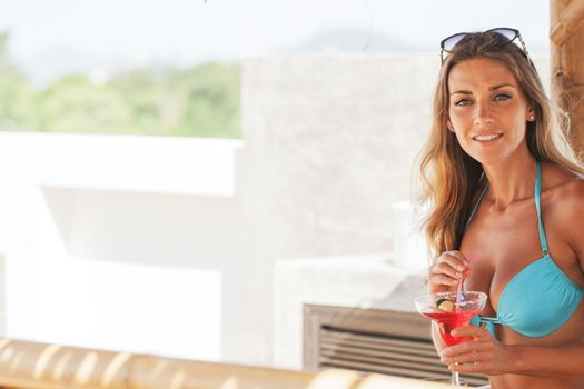 Girl in bikini on vacation drinking cocktail and smiling