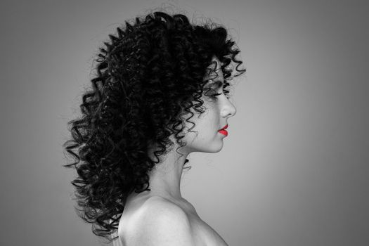 Profile portrait of young caucasian woman with curly hair and red lips