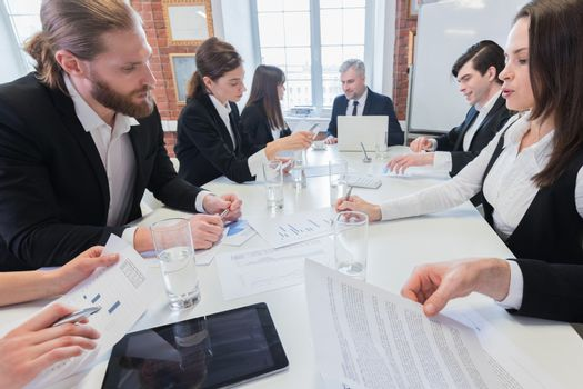Group of many business people working together in office with financial reports