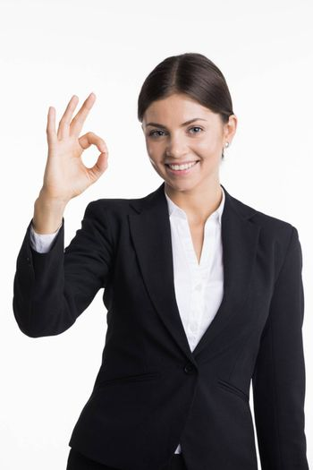Confident young smiling businesswoman showing OK sign isolated on white background