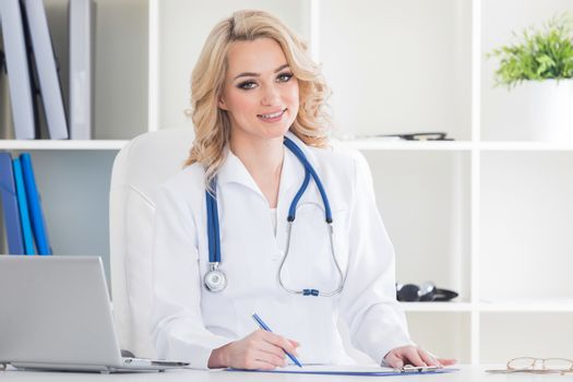 Young therapeutis female doctor writing prescription at desk in hospital office