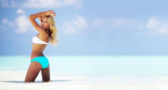 Beautiful woman in bikini relaxing in water at tropical beach at Maldives