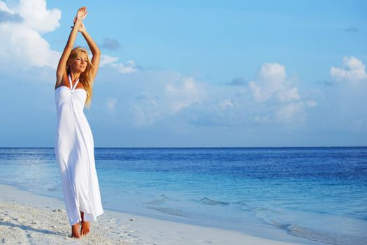 Young woman wearing a white dress standing on a beach and enjoying vacation