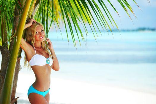 Woman in bikini under palm tree on blue sea background