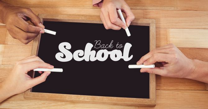 Digital composite of Hands writing back to school on blackboard