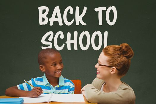 Digital composite of Student boy and teacher at table against green blackboard with back to school text