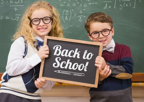 Digital composite of back to school text on blackboard with two school kids