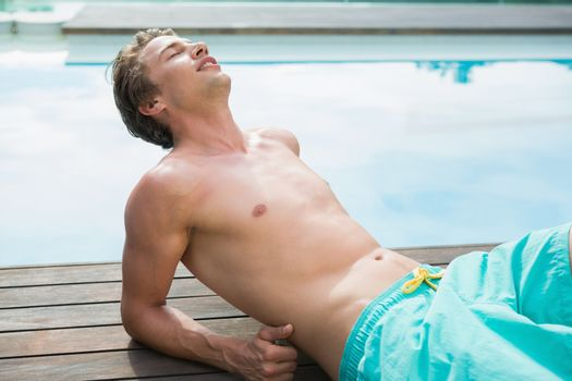 Man lying by the swimming pool on a sunny day