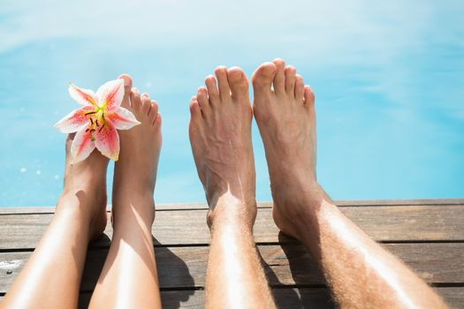 Close up of couples bare feet against swimming pool on a sunny day
