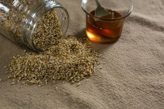Grains spilling out of jar with bowl of honey