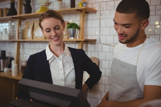 Waiter with owner looking into cash register in cafe