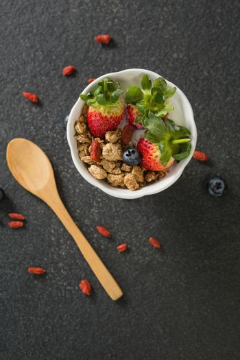 Bowl of breakfast cereals and fruits with spatula on black background