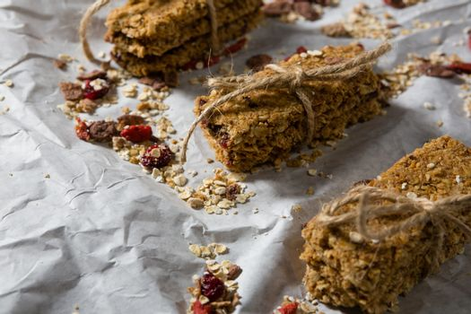 Granola bars tied with string on wax paper
