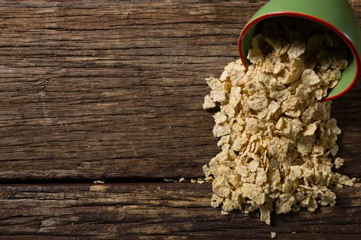 Muesli spilling from bowl on the wooden table