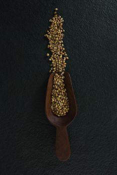 Coriander seeds in a wooden scoop
