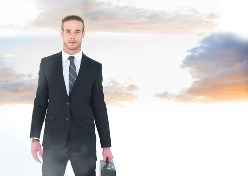 Businessman holding briefcase in twilight sky